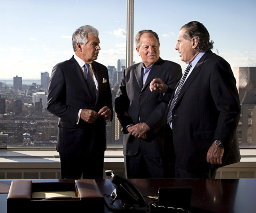 Three managing partners at DHC having a discussion in the boardroom