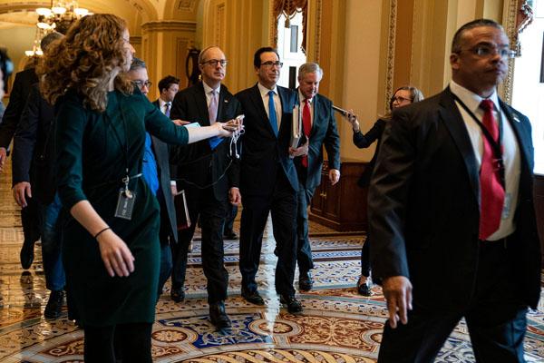Treasury Secretary Steve Mnuchin, center, heading to meet the Senate minority leader, Chuck Schumer, in Washington on Tuesday.